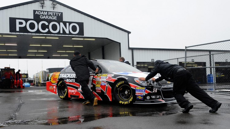 Crew members push the #14 Mobil 1/Bass Pro Shops Chevrolet of Tony Stewart in the garage area during a rain delay at Pocono Raceway on June 7, 2013 in Long Pond, Pennsylvania. (Credit: Jared C. Tilton/Getty Images)