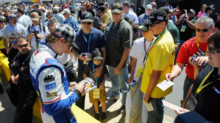 Travis Pastrana, driver of the #60 Roush Fenway Racing Ford, signs autographs for fans on pit road during qualifying for the NASCAR Nationwide Series History 300 at Charlotte Motor Speedway on May 25, 2013 in Concord, North Carolina. (Photo by Jared C. Tilton/Getty Images)