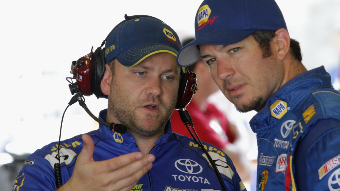 Martin Truex Jr.(R), driver of the #56 NAPA Auto Parts Toyota, talks with his crew chief Chad Johnston during practice for the NASCAR Sprint Cup Series Samuel Deeds 400 At The Brickyard at Indianapolis Motor Speedway on July 27, 2013 in Indianapolis, Indiana. (Credit: Jerry Markland/Getty Images)