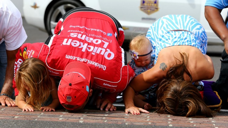 Ryan Newman, driver of the #39 Quicken Loans/The Smurfs Chevrolet, and his family kiss the bricks after winning the NASCAR Sprint Cup Series Samuel Deeds 400 At The Brickyard at Indianapolis Motor Speedway on July 28, 2013 in Indianapolis, Indiana. (Credit: Streeter Lecka/NASCAR via Getty Images)