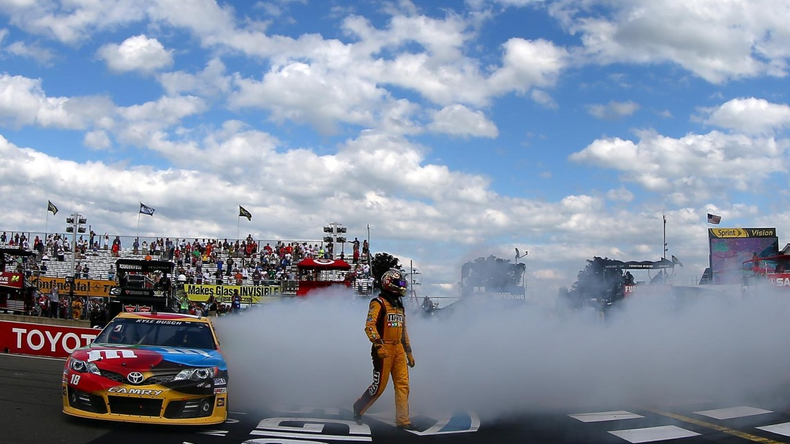 Kyle Busch, driver of the #18 M&M's Toyota, celebrates with a burnout after winning the NASCAR Sprint Cup Series Cheez-It 355 at The Glen at Watkins Glen International on August 11, 2013 in Watkins Glen, New York. (Credit: Todd Warshaw/Getty Images)