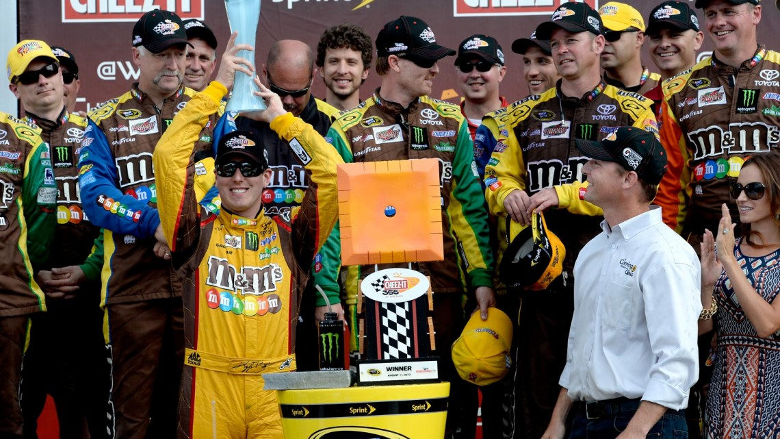 Kyle Busch, driver of the #18 M&M's Toyota, celebrates in victory lane after winning the NASCAR Sprint Cup Series Cheez-It 355 at The Glen at Watkins Glen International on August 11, 2013 in Watkins Glen, New York. (Credit: John Harrelson/NASCAR via Getty Images)