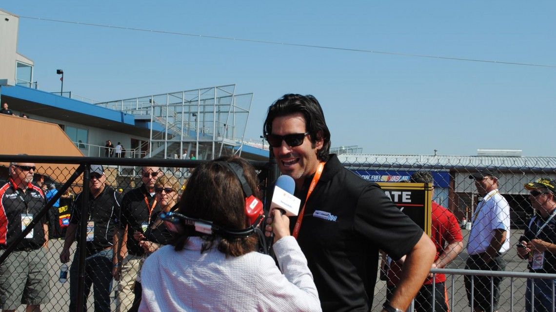 Carter Oosterhouse speaks with Claire B. Lang at Michigan International Speedway in Brookyln, MI (Credit: Heather Baker for The Fast and the Fabulous)