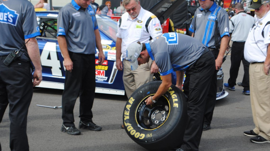 Ron Malec and Chad Knaus look over a tire with their team at Michigan International Speedway in Brookyln, MI (Credit: Heather Baker for The Fast and the Fabulous)