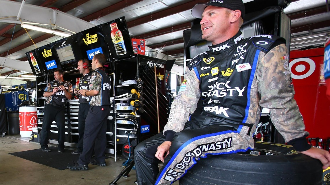 Clint Bowyer, driver of the #15 PEAK/Duck Dynasty Toyota, sits in the garage during practice for the NASCAR Sprint Cup Series Cheez-It 355 at Watkins Glen International on August 9, 2013 in Watkins Glen, New York. (Credit: Jonathan Ferrey/NASCAR via Getty Images)