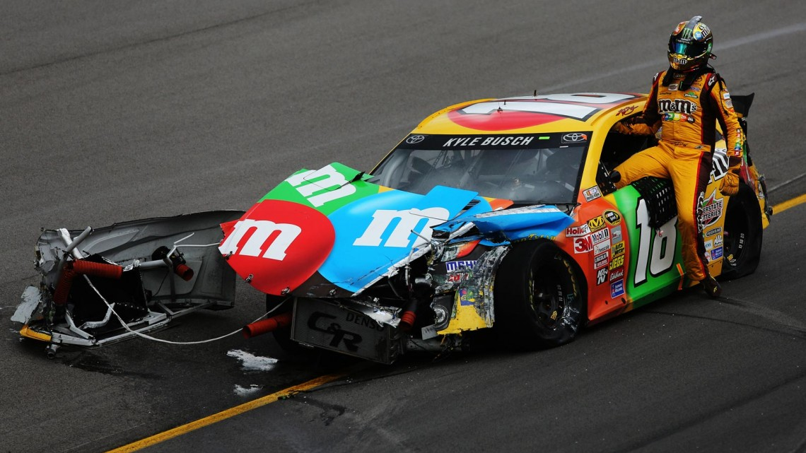 Kyle Busch, driver of the #18 M&M's Toyota, climbs from his car after an on-track incident during the NASCAR Sprint Cup Series 13th Annual Hollywood Casino 400 at Kansas Speedway on October 6, 2013 in Kansas City, Kansas. (Credit: Ed Zurga/Getty Images)