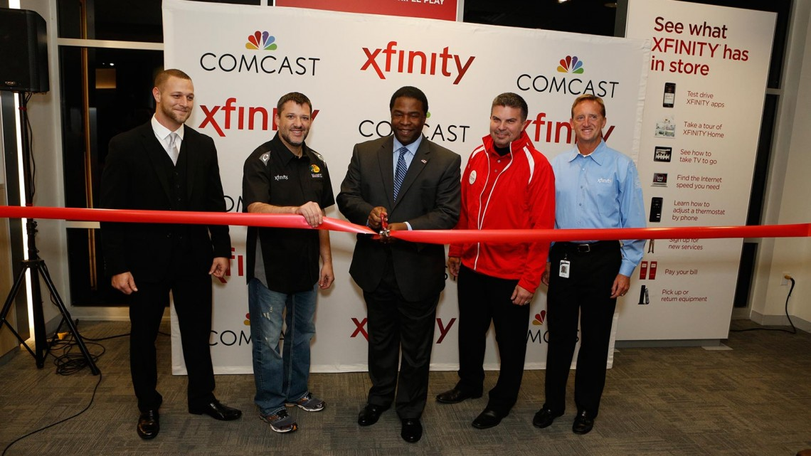 Jacksonville, Florida, Mayor Alvin Brown (center) cuts the grand-opening ribbon along with NASCAR driver Tony Stewart (second from left) and Comcast executives on Wednesday, January 8, 2014, during a special event celebrating the new River City Xfinity® store location in Jacksonville, Florida. (Credit: Comcast Florida/Dan Van Slyke, Jr.)