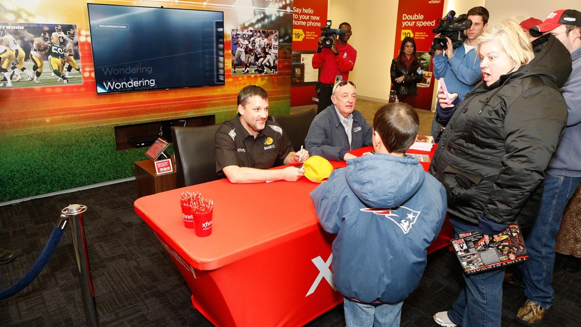 Tony Stewart, driver of the No. 14 Bass Pro Shops/Mobil 1 Chevrolet in the NASCAR® Sprint Cup Series™, greets the first fan in line to get his autograph on Wednesday, January 8, 2014, during the grand-opening celebration of the new River City Xfinity® store location in Jacksonville, Florida. Keegan, age 8, traveled from Ambrose, Georgia, with his mom (also pictured) to meet his racing hero and patiently waited in line for more than nine hours to ensure his pole-position spot (Photo credit: Comcast Florida/Dan Van Slyke, Jr.).
