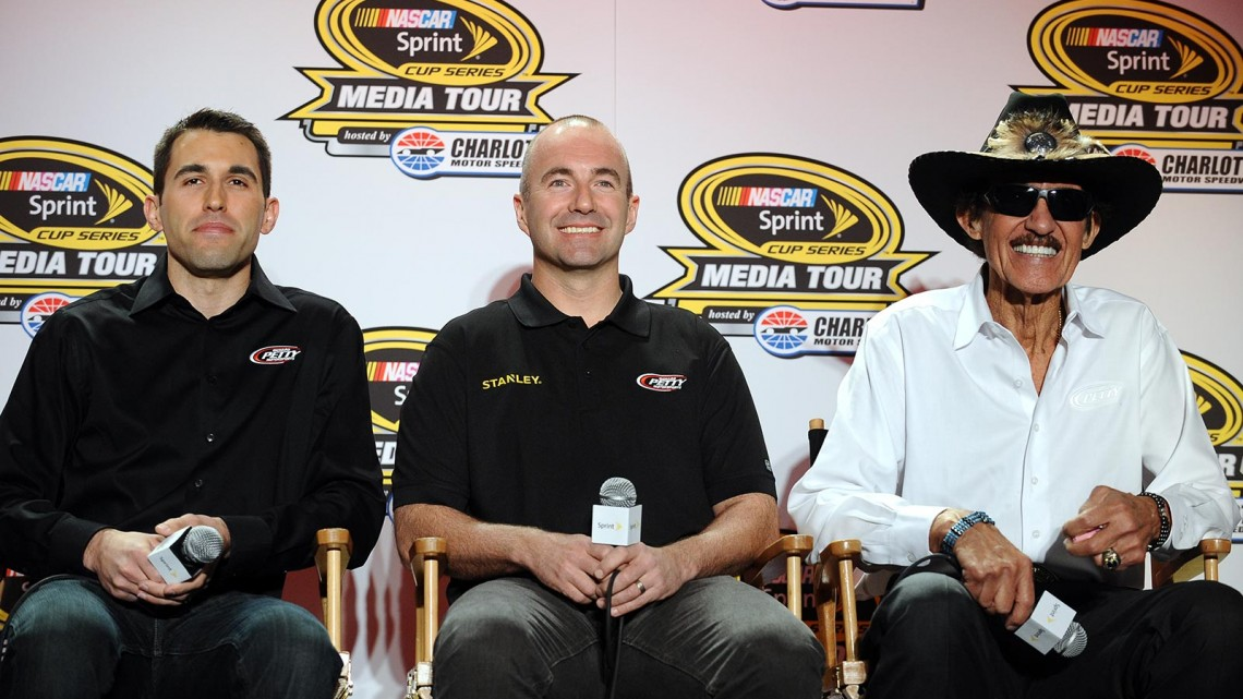 Aric Almirola, driver of the No. 43 Smithfield Ford, and Marcos Ambrose, driver of the No. 9 Stanley Ford, and Richard Petty look on during the NASCAR Sprint Media Tour at Charlotte Convention Center on January 29, 2014 in Charlotte, North Carolina. (Credit: Rainier Ehrhardt/Getty Images)