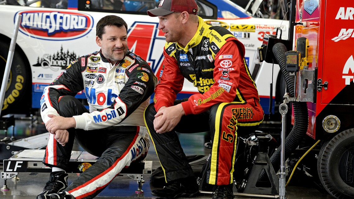 Tony Stewart, driver of the #14 Bass Pro Shops / Mobil 1 Chevrolet, (L) and Clint Bowyer, driver of the #15 5-hour ENERGY Toyota, talk to one another the garage during NASCAR Sprint Cup Series testing at Las Vegas Motor Speedway on March 6, 2014 in Las Vegas, Nevada. (Credit: 295905Patrick Smith/NASCAR via Getty Images)