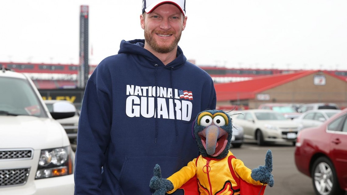 Dale Earnhardt Jr., driver of the #88 National Guard Chevrolet, and The Great Gonzo are seen in the garage area prior to the NASCAR Sprint Cup Series Auto Club 400 at Auto Club Speedway on March 23, 2014 in Fontana, California.  (Credit: NASCAR Via Getty Images)