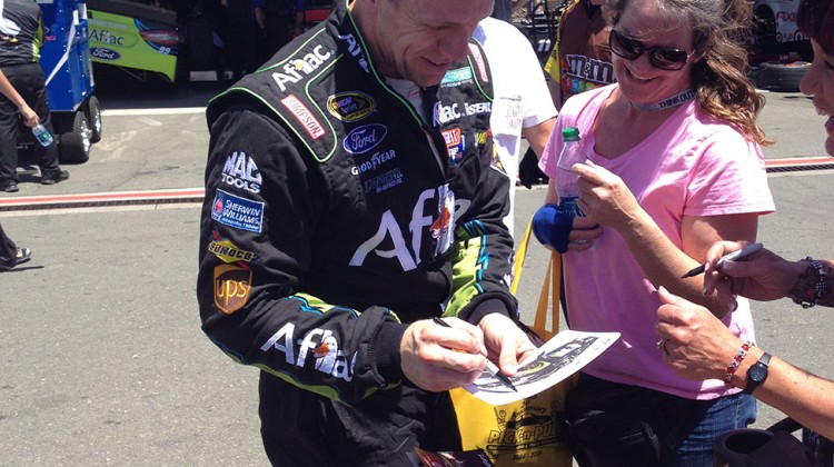 Carl Edwards signs autographs for a cat at Sonoma Raceway on Friday, June 20, 2014. (photo credit: The Fast and the Fabulous)