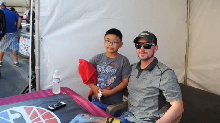 Michael Annett takes a picture with a young fan at Napa NASCAR Night in Downtown Napa on Saturday, June 21st, 2014. (photo credit: Heather Baker/The Fast and the Fabulous)