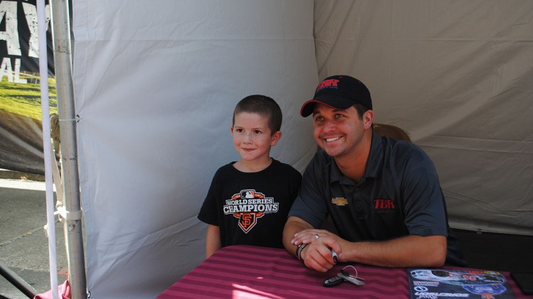 Reed Sorenson takes a photo with a young fan at the Napa NASCAR Night event in Dowtown Napa on Saturday, June 21st, 2014. (photo credit: Heather Baker/The Fast and the Fabulous)