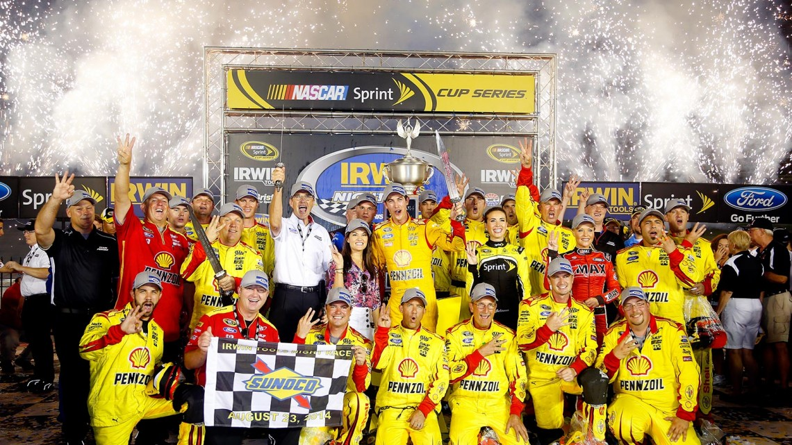 Joey Logano, driver of the #22 Shell Pennzoil Ford, and his team celebrate in Victory Lane after winning the NASCAR Sprint Cup Series Irwin Tools Night Race at Bristol Motor Speedway on August 23, 2014 in Bristol, Tennessee. (Credit: 300865Matt Sullivan/NASCAR via Getty Images)