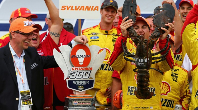 Joey Logano, driver of the #22 Shell-Pennzoil Ford, receives a lobster in victory lane after winning the NASCAR Sprint Cup Series Sylvania 300 at New Hampshire Motor Speedway on September 21, 2014 in Loudon, New Hampshire. (Credit: Jonathan Ferrey/NASCAR via Getty Images)