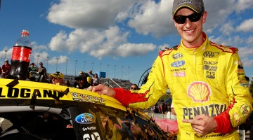 Joey Logano, driver of the #22 Shell-Pennzoil Ford, celebrates in Victory Lane after winning the NASCAR Sprint Cup Series Hollywood Casino 400 at Kansas Speedway on October 5, 2014 in Kansas City, Kansas. (Credit: Brian Lawdermilk/NASCAR via Getty Images)