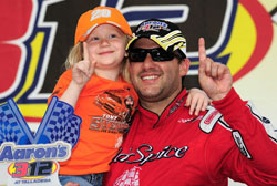 Tony Stewart celebrates with Britney Brewster in victory lane after winning the NASCAR Nationwide Series Aarons 312 at Talladega Superspeedway (Photo Credit: Rusty Jarrett/Getty Images for NASCAR)
