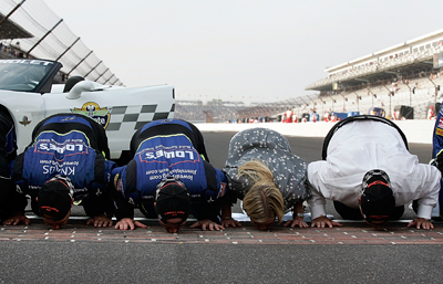 (L-R): Crew chief Chad Knaus, Jimmie Johnson, Chandra Johnson and owner Rick Hendrick kiss the yard of bricks after winning the Allstate 400 at the Brickyard. (Photo Credit: Jason Smith/Getty Images for NASCAR)