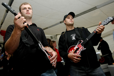 Travis Kvapil and David Gilliland play at a Guitar Hero: Aerosmith demonstration at the Target Chip Ganassi Racing hospitality tent at New Hampshire Motor Speedway on Saturday night (Photo Credit: Chris McGrath / Getty Images for NASCAR)
