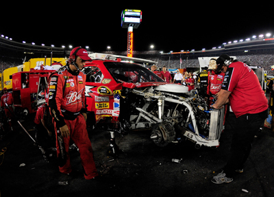 Kasey Kahne's crew works on his No. 9 Budweiser Dodge after a seven car accident on Lap 216. Kahne finished 40th and dropped from 11th to 14th in the standings. (Photo Credit: Rusty Jarrett/Getty Images for NASCAR)
