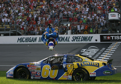 Carl Edwards, driver of the No. 60 Planters Ford, celebrates a win in his typical manner -- a backflip -- but this time kept his helmet on. Edwards, who also was the polesitter, won the NASCAR Nationwide CARFAX 250 on Saturday at Michigan International Speedway. (Photo Credit: Marc Serota/Getty Images for NASCAR)
