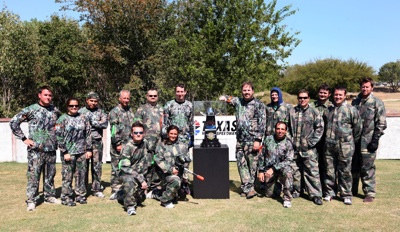 NASCAR Sprint Cup Series star Kyle Busch (immediate left of trophy) and Texas Motor Speedway President Eddie Gossage (immediate right of trophy) stand next to the Dickies 500 trophy and the participants in paintball warfare for a Texas Motor Speedway media event Tuesday, Sept. 30, at Fun On The Run Paintball Park in Fort Worth, Texas.