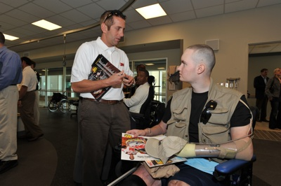(Left to right) NASCAR Sprint Cup Series driver Greg Biffle signs an autograph for a soldier at Walter Reed Army Medical Center's Military Advance Training Center in Washington, D.C. NASCAR made its annual visit to the facility to salute the troops on Thursday. (Photo Credit: Larry French/Getty Images for NASCAR)