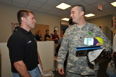 (Left to right) NASCAR Sprint Cup Series driver Scott Riggs visits a soldier at Walter Reed Army Medical Center in Washington, D.C. NASCAR made its annual visit to the facility to salute the troops on Thursday. (Photo Credit: Larry French/Getty Images for NASCAR)