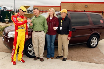 Kevin Harvick, driver of the No. 29 Shell-Pennzoil Chevrolet, presents a minivan to Robert Ard, the son of former Nationwide Series Champion Sam Ard, while DeLana Harvick and Jim Hunter, Vice President of Corporate Communications for NASCAR join them outside the Media Center, prior to practice for the NASCAR Sprint Cup Series Pep Boys Auto 500 at Atlanta Motor Speedway on Saturday. (Photo Credit: Chris Graythen/Getty Images)