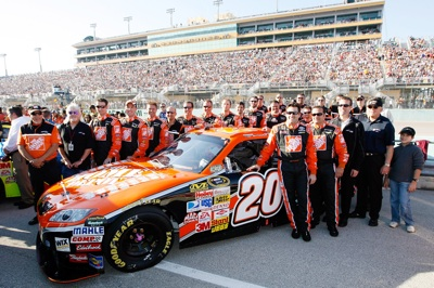 Tony Stewart poses with crew chief Greg Zipadelli, team owners J.D. Gibbs and Joe Gibbs and crew members of his No. 20 Home Depot Toyota before his 356th and final start for Joe Gibbs Racing. Stewart finished ninth, his 207th top-10 finish. (Photo Credit: John Harrelson/Getty Images for NASCAR)