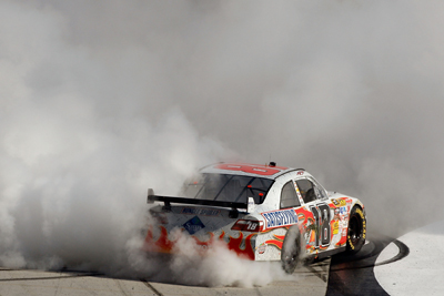 Kyle Busch does a burnout on the frontstretch of Bristol Motor Speedway to celebrate his Food City 500 victory. (Photo Credit: Chris Graythen/Getty Images)
