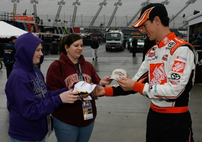 Joey Logano signs autographs for two fans while waiting out a rain delay at Martinsville Speedway. (Photo Credit: Geoff Burke/Getty Images)