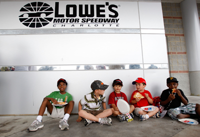 A group of kids enjoy some Domino's pizza while waiting out the rain delay at Lowe's Motor Speedway. (Photo Credit: Streeter Lecka/Getty Images for NASCAR)