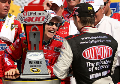 Mark Martin, driver of the No. 5 CARQUEST/Kellogg's Chevrolet, is congratulated in victory lane by teammate Jeff Gordon, driver of the No. 24 DuPont/National Guard 'Year of the NCO' Chevrolet, after Martin wins the NASCAR Sprint Cup Series LifeLock 400 at Michigan International Speedway on Sunday in Brooklyn, Mich. Gordon finished second. (Photo Credit: Ezra Shaw/Getty Images)