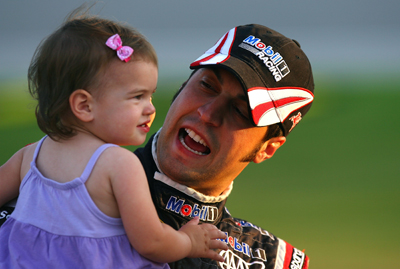 Sam Hornish Jr., driver of the No. 77 Mobil 1 Advanced Fuel Economy Dodge, shares a smile with daughter Addison while standing on pit road waiting to qualify for the Saturday's NASCAR Sprint Cup Series LifeLock.com 400 at Chicagoland Speedway in Joliet, Ill. (Photo Credit: Jason Smith/Getty Images for NASCAR)