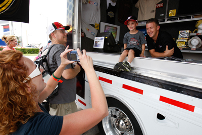 NASCAR Sprint Cup Series driver AJ Allmendinger meets a fan as his mother takes a picture at the NASCAR Sprint Cup Series Merchandise Hauler on Friday at Daytona International Speedway. (Photo Credit: Streeter Lecka/Getty Images)