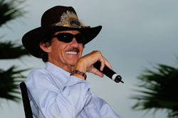 Seven-time NASCAR Sprint Cup Series champion Richard Petty talks with fans during a question-and-answer session at the the Sprint FanZone stage in the Daytona International Speedway infield Friday. Petty celebrates the 25th anniversary of his final and NASCAR Sprint Cup Series record 200th victory on July 4, 1984 at the track. (Photo Credit: Sam Greenwood/Getty Images)