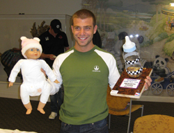 E.J. Viso with a baby doll and the winners trophy after winning the Daddy Boot Camp challenge (credit: Infineon Raceway)