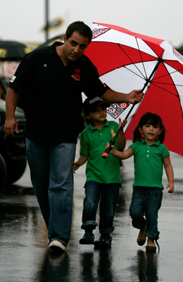 Juan Pablo Montoya, driver of the No. 42 Target Chevrolet, in the NASCAR Sprint Cup Series, shields his son and daughter before the Heluva Good! Sour Cream Dips at The Glen on Sunday at Watkins Glen International in Watkins Glen, N.Y. The race was postponed by rain to Monday at noon ET. (Photo Credit: Todd Warshaw/Getty Images for NASCAR)
