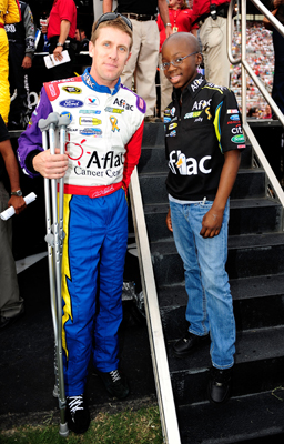 Carl Edwards, driver of the No. 99 Aflac Cancer Center Ford, stands with Jody Lawrence, a 13-year-old cancer patient from Atlanta who designed the color scheme for his Sprint Cup Series car for the NASCAR Sprint Cup Series Pep Boys Auto 500 at Atlanta Motor Speedway in Hampton, Ga. (Photo Credit: Rusty Jarrett/Getty Images for NASCAR)