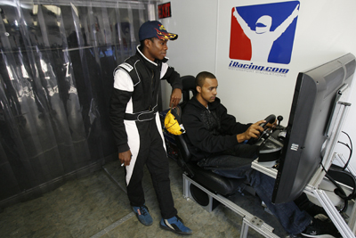 Dylan Smith of Randolph, Vt., watches Michael Cherry of Valrico, Fla., make laps on an iRacing simulator at Motor Mile Speedway. (Photo Credit: Tom Whitmore/Getty Images for NASCAR)