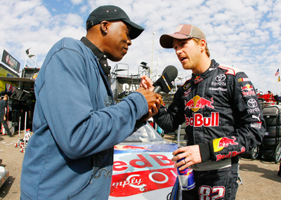 Arsenio Hall interviews Scott Speed at Phoenix International Raceway for a segment for the Jay Leno Show. (Photo Credit: Jason Smith/Getty Images for NASCAR)