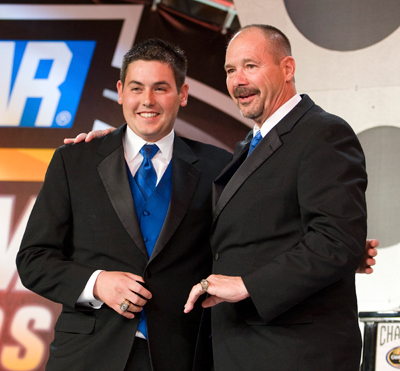 George Brunnhoelzl III (left) presents his father, George Jr. with a matching championship ring. (Photo Credit: Chris Keane/Getty Images for NASCAR)