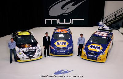 (Left to right) Michael Waltrip Racing's NASCAR Sprint Cup Series drivers David Reutimann, Michael Waltrip and Martin Truex Jr. pose with their rides Wednesday at MIchael Waltrip Racing in Cornelius, N.C. during the NASCAR Sprint Media Tour. (Credit: Jason Smith/Getty Images)