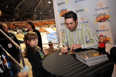 A young fan meets NASCAR Sprint Cup Series driver Elliott Sadler and gets an autograph on Saturday during the Sprint Sound and Speed Fan Festival at Nashville Municipal Auditorium in Nashville, Tenn. (Credit: Grant Halverson/Getty Images for NASCAR)