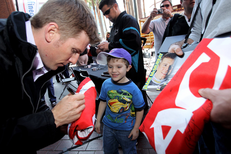 Daytona 500 champion Jamie McMurray signs an autograph for a young fan during his victory tour of San Francisco on February 17, 2010 in San Francisco, California. (Photo by Ezra Shaw/Getty Images)
