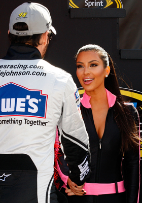 Television personality Kim Kardashian (R) greets Jimmie Johnson (L), driver of the #48 Lowes/Kobalt Tools Chevrolet on stage prior to the NASCAR Sprint Cup Series Shelby American at Las Vegas Motor Speedway on February 28, 2010 in Las Vegas, Nevada. (Photo by Geoff Burke/Getty Images for NASCAR)