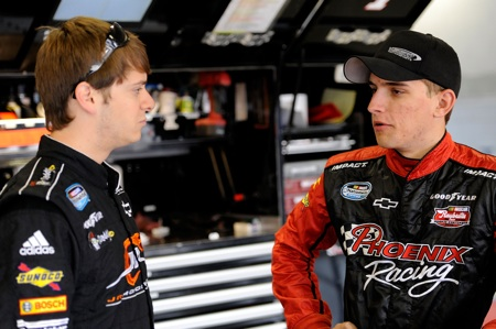 (Left to right) Landon Cassill and Plano, Texas native James Buescher talk in the NASCAR Nationwide Series garage during practice Friday at Texas Motor Speedway in Fort Worth, Texas. (Credit: John Harrelson/Getty Images for NASCAR)