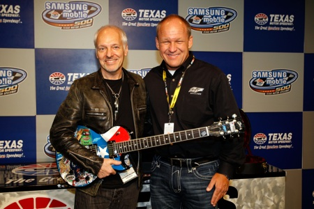 Musician Peter Frampton poses with artist Sam Bass and the special guitar Bass created for him in the deadline room Sunday at Texas Motor Speedway. (Credit: Chris Graythen/Getty Images)